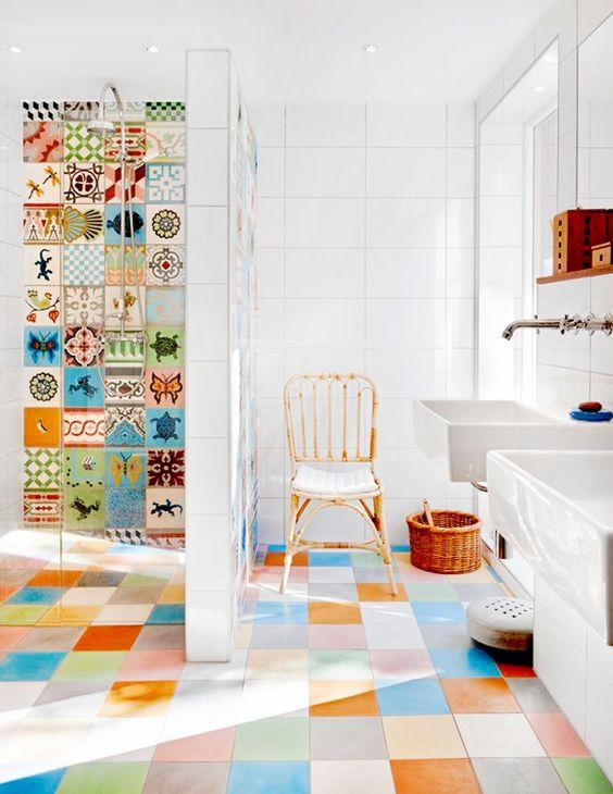#reforma #baño con 2 lavabo sin pedestal, zona de ducha con pared de separación y puerta de vidrio, paredes de baldosa hidráulica y suelo de colores.