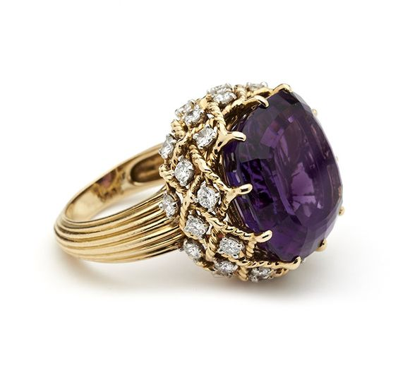 Ring, Cartier, c.1950.Gold, amethysts and Diamonds. Mounted with a large amethyst in a gold rope twist gallery hung with brilliant cut diamonds, to reeded gold shank Cartier, Paris, Signed, Hallmarked and Numbered