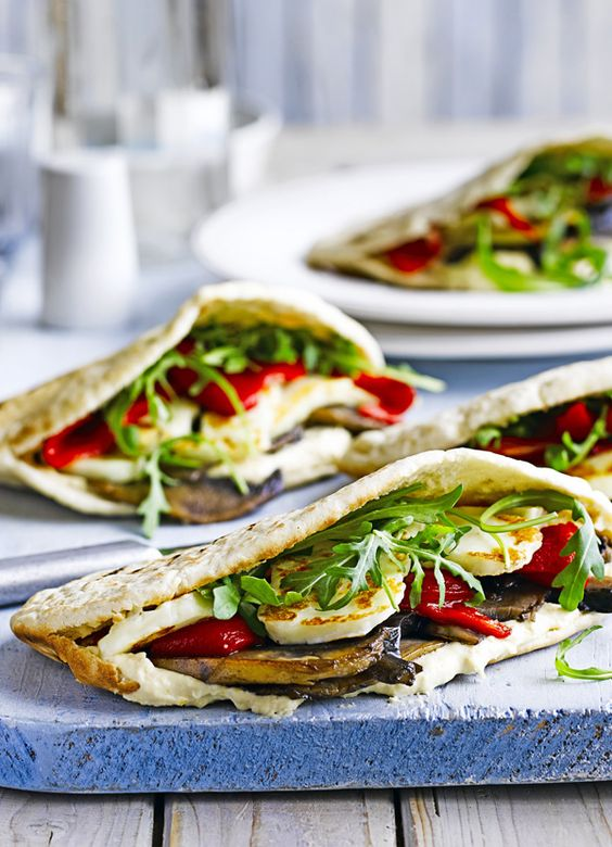 Stuffed mushroom and halloumi pittas. Quick idea for a vegetarian sandwich: pittas stuffed with grilled halloumi, humous, mushrooms and peppers with rocket. Ready quickly in 15 minutes.