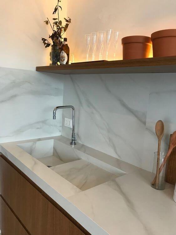 Pia de mármore na cozinha branca com prateleira de madeira #piademármore #piademármorebanheiro #piademármorecozinha