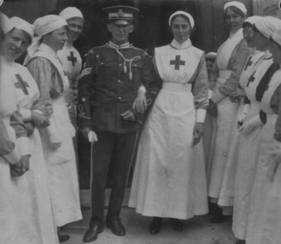 A Red Cross nurse and her soldier groom prepare to walk past a line of Red Cross VAD nurses at their wedding during the First World War