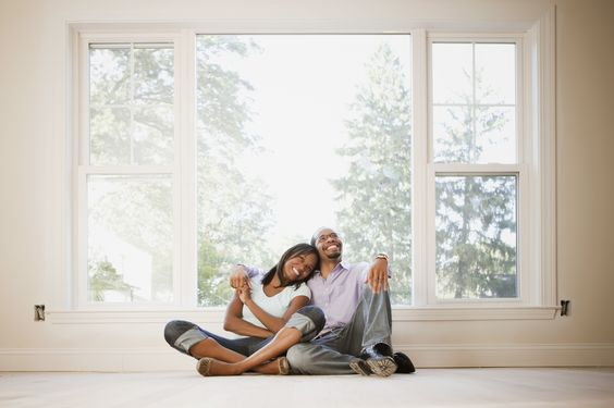 Black couple sitting on floor of empty room