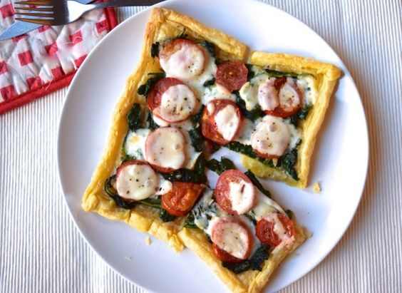 Supersnelle spinaziepizza (1 persoon): 4 plakjes bladerdeeg, ontdooid  - 100 gram verse spinazie  - 1 teen knoflook  - 2 tomaten  - een half bolletje mozzarella