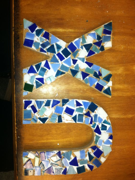 tiles/shards of glass, could cover the letters in aluminum foil glues to wood :)