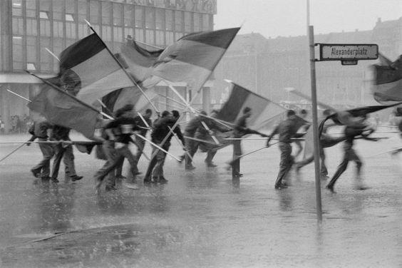 1.-Mai-Demonstration am Alexanderplatz 1987: Ein Regenschauer bringt für einen Moment die vorgesehene Ordnung und das übliche Ritual der Unterwerfung durcheinander.