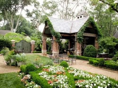 This looks fantastic.... A quaint, brick pavilion with vines winding up along the roofline creates a lovely garden spot. A fireplace provides cozy warmth. Absolutely charming!
