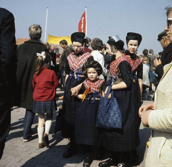 Meisjes op de jaarmarkt te Staphorst. De jaarmarkt wordt gehouden op de derde dinsdag van april. Het kleinste meisje draagt de 'nette' (zwarte kindermuts) De drie grotere meisjes dragen reeds het zilveren oorijzer, doch zonder de gouden 'krullen'. Hier uit is op te maken dat het kleine meisje jonger is dan 7 jaar terwijl de andere drie meisjes tussen de 7 en 12 jaar oud zijn. Geen van de vier is in de rouw. 1964-1965 #Overijssel #Staphorst