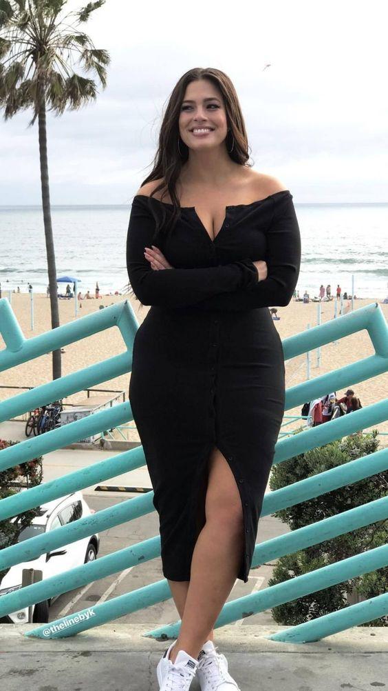 Mujer curvy con vestido negro largo y tenis blancos