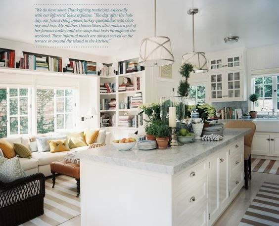 Possibly the most perfect kitchen/sitting area. Nice island with cabinets, lots of windows, decorative yet useful shelves for cookbook storage...