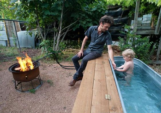 Jesse Hartman keeps son Harvey company at the pool, a galvanized stock tank that can be kept cool or warmed with a heat lamp or a pump that circulates the water through a coil on the grill. (Photo by Mark Matson for American Statesman)