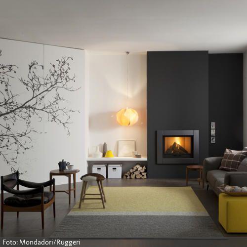 Der elegante Look dieses Wohnzimmers wird durch klare Formen und gedeckte Farben geprägt. Das Wandtattoo mit Baummotiv sorgt für einen verspielten Kontrast.