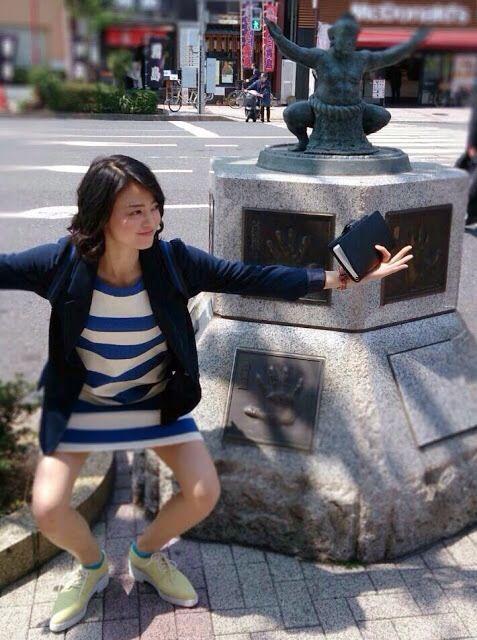 銅像の前で同じポーズをしている小林涼子の画像