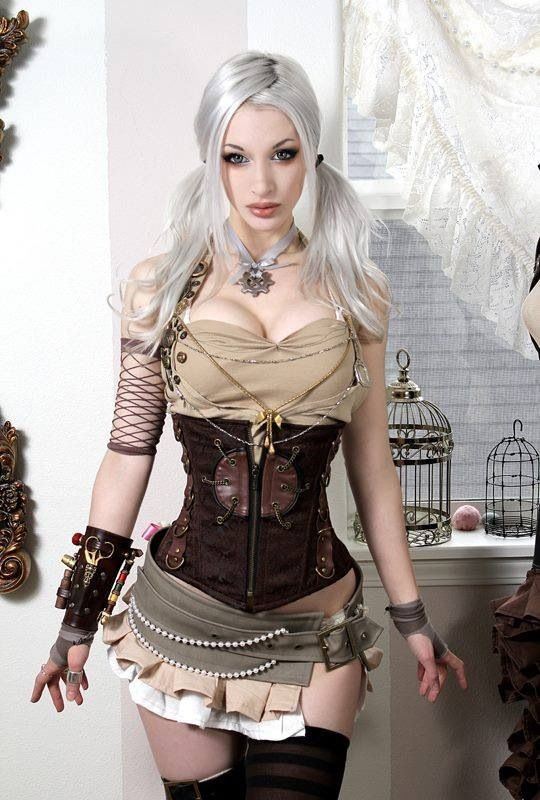 Steampunk couture with new mixtures of netting on arms with leather wrist weapons support & 1/2 gloves. Very detailed bustier with layers of chains & necklaces combined with a side strap, super short, multi-ruffle skirt adorned with pearls as a softer element.