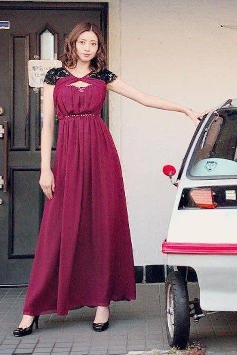 ワインレッドのワンピースを着て車の横に立っている片瀬那奈の画像