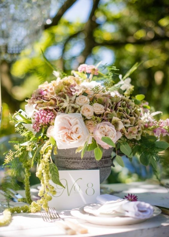 Garden wedding floral centrepiece in a stone urn with garden roses and trailing foliage