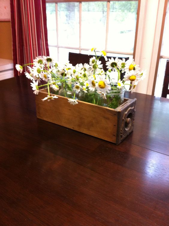 June centerpiece in the Lowe home.  Love this antique drawer....with glass jars filled with lovely daisies!
