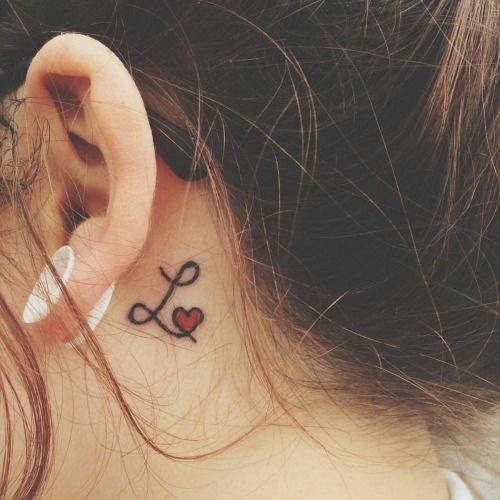 Little behind the ear tattoo of letter L together with a red...