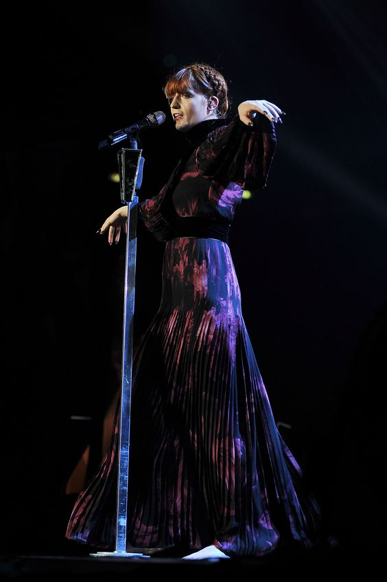 Florence Welch wore a Gucci Fall/Winter 2012-13 custom made burgundy printed silk georgette long sleeve pleated gown to perform as part of her Ceremonials European Tour on November 20, 2012 in Milan, Italy.