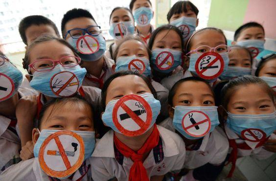 Un grupo de niños llevan máscaras con signos de no fumar para apoyar el día mundial sin tabaco en una escuela primaria de Handan, provincia de Hebei del norte de China._EL PAÍS