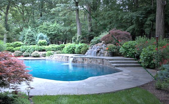 Inground pool landscaping with fencing completed for Swimming pool waterfalls construction