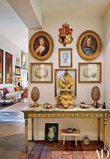 Paintings of Swedish nobility, a Russian coat of arms and renderings of silver pieces hang in a hall between the great room and kitchen. Cone finials and an Indian sculpture are on the French console | archdigest.com