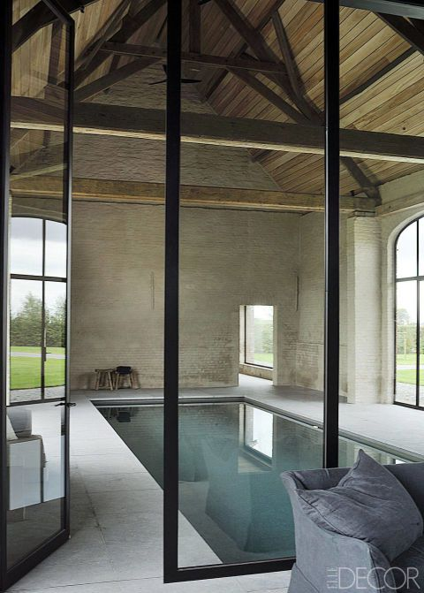 """""""You need these imperfections to surprise people, to make things not too predictable,"""" he says. """"That's the essence of this project. Once you step inside, it's anything but a conventional farm house.""""  The poolhouse in a former barn features steel frames and original beams; the pool is sheathed with glass mosaic tiles, and the surround is Belgian bluestone."""