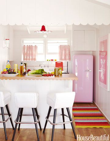 pink and white kitchen in a small beach cottage featuring a pink fridge