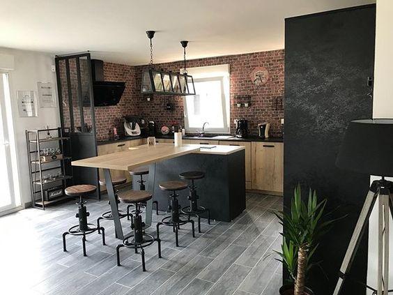 Verrière, brique, tabourets en métal, cette cuisine noire et bois reprend tous les codes du style industriel