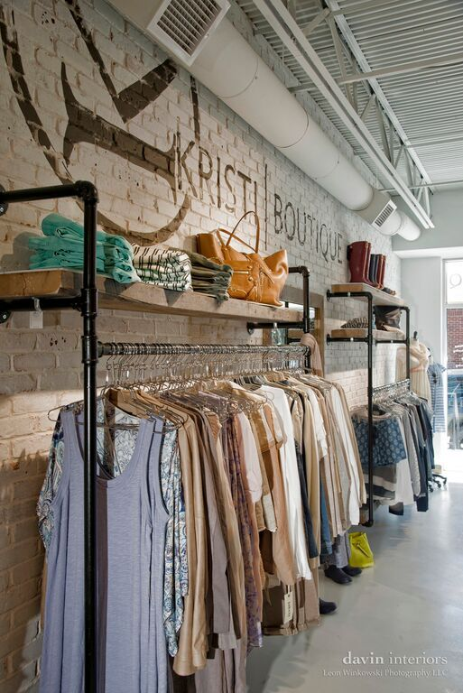wall logo monogram pipe part clothing rack painted brick white brick rustic brick wall concrete floor boutique clothing store