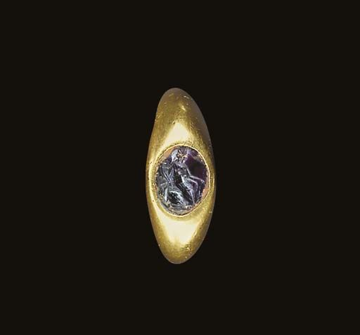 A ROMAN GOLD AND AMETHYST FINGER RING  Circa 2nd Century A.D.  The hollow hoop round in section, expanding at the shoulders, the bezel set with a flat oval stone engraved with a seated Fortuna, the draped goddess holding a cornucopia and a ship's rudder 7/8 in. (2.2 cm.) wide; ring size 4