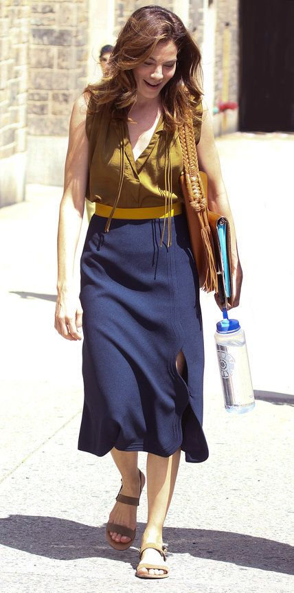 Michelle Monaghan's style is equal parts effortless and sophisticated. Case in point: Her recent ensemble, in which she color-blocked with an olive green blouse tucked into the yellow waistband of a navy midi-length skirt and styled it out with an Altuzarra holdall and flat neutral sandals.