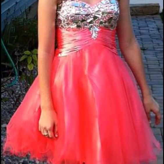 Homecoming and Prom dress Coral homecoming/prom dress. Laces up in the back and has a mesh skirt with headed top. Super cute! Dresses Strapless