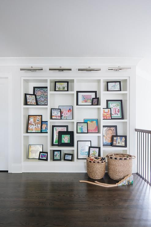 Picture Lights Illuminate White Built In Shelves Styled With Black Framed Art And Fixed In A Second Floor Dark Stained Wood Floors Built In Bookcase Wall Decor