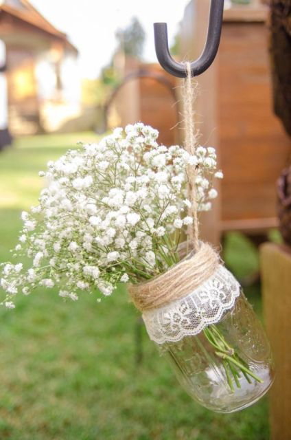 Twine and lace around a hanging mason jar with baby's breath.