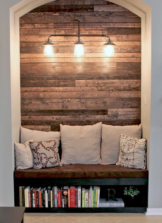 Cozy reading nook with wood plank wall.