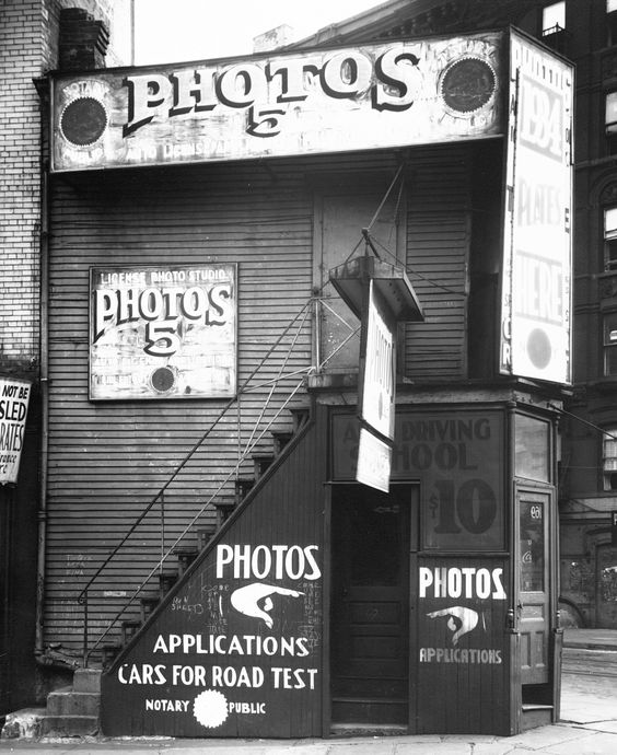 Walker Evans: License Photo Studio, New York, 1934  This photograph displays Walker Evans' increasingly assured ability to construct meaning out of the juxtaposition of pictorial elements. Here they extend from the hands pointing to the doorway, to the crazy quilt of signs papered across the building's facade, to graffiti scrawled among the signs. Many of Evans' most sophisticated photographs from the period have a rebuslike quality, disclosing previously unnoticed connecti...