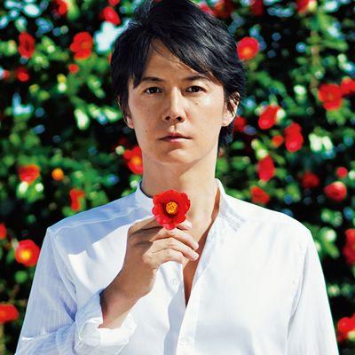 赤い花に囲まれる福山雅治