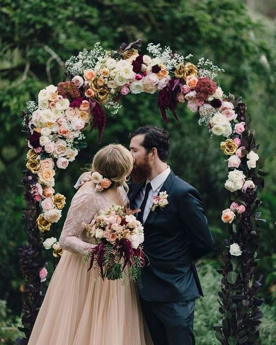 The bride's blush wedding dress complements the neutral roses and eggplant hues in this dark-leaved rustic wedding arch.