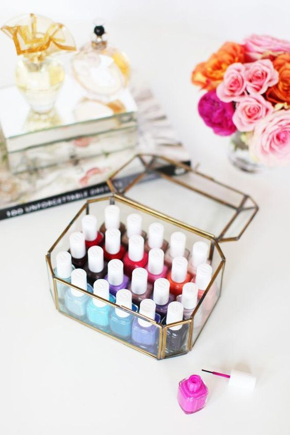 Beauty Product Organization: 10 Chic Ways to Decorate Your Vanity - nail polish in a decorative glass box—organized by color, and in the company of pink roses: