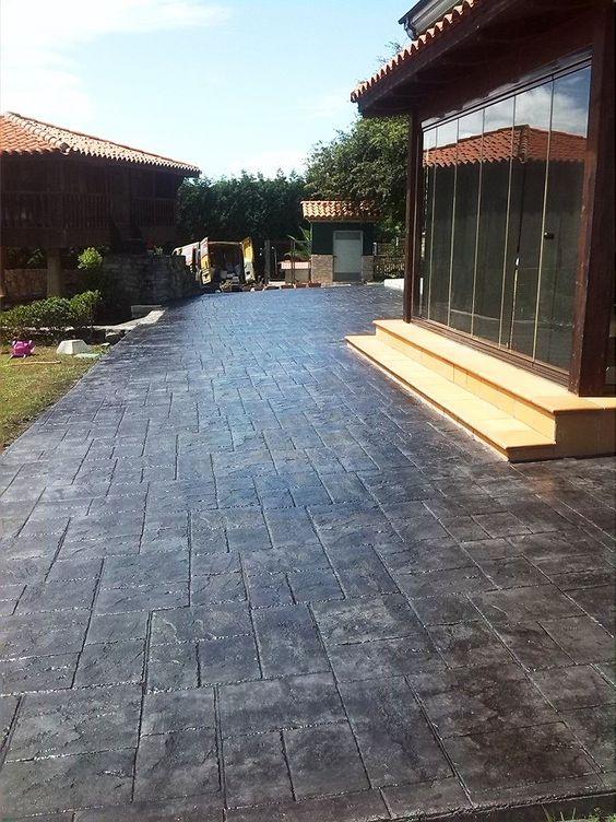Entrada a casa asturiana con pavimento de hormigón impreso en textura piedra covadonga y ankare zaline gris pizarra