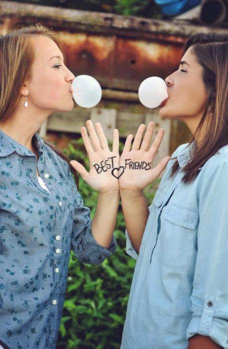 Chicas mascando chicle y mostrando sus manos con la frase best friends