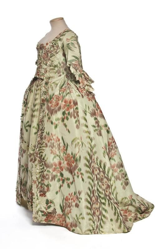Side view, robe à la française, France, c. 1760. Chiné woven silk, lined with linen. With a pattern of red flowers on green foliage and maroon floral sprays.
