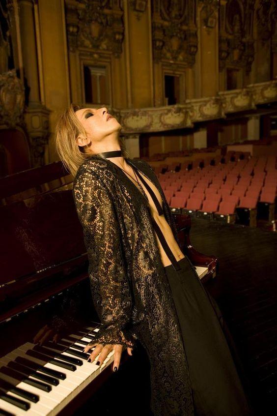 シースルーのロングコートを着てピアノの前に立つXJAPAN・YOSHIKIの画像