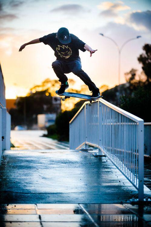 橋の柵にスケートボードで乗る男性