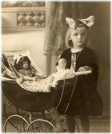 Little girl with dolls in pram: