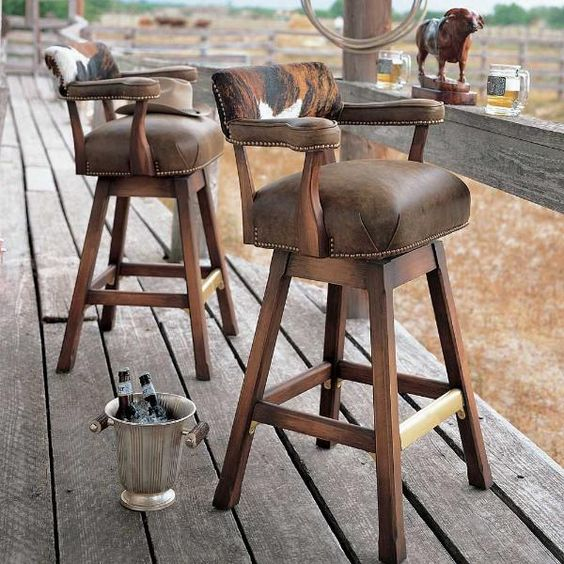 Add a touch of ranch to your bar with rustic hardwood swivel bar stools featuring rich brown leather upholstery trimmed with brass nails and cowhide backs | King Ranch Saddle Shop