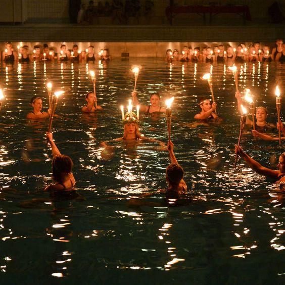 Niñas y adolescentes de un grupo de nado sincronizado hacen una presentación en Estocolmo, Suecia para celebrar el día de Santa Lucía.
