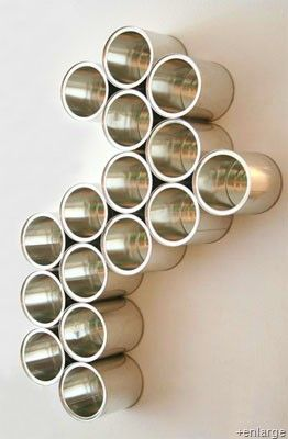Upcycled Cans Make Great Wall Art / Organizer- Gather up a bunch of old cans. Peel the labels off and clean them. Arrange them into whatever shape you like. Glue them together with some green glue. Dry and hang with a screw or two