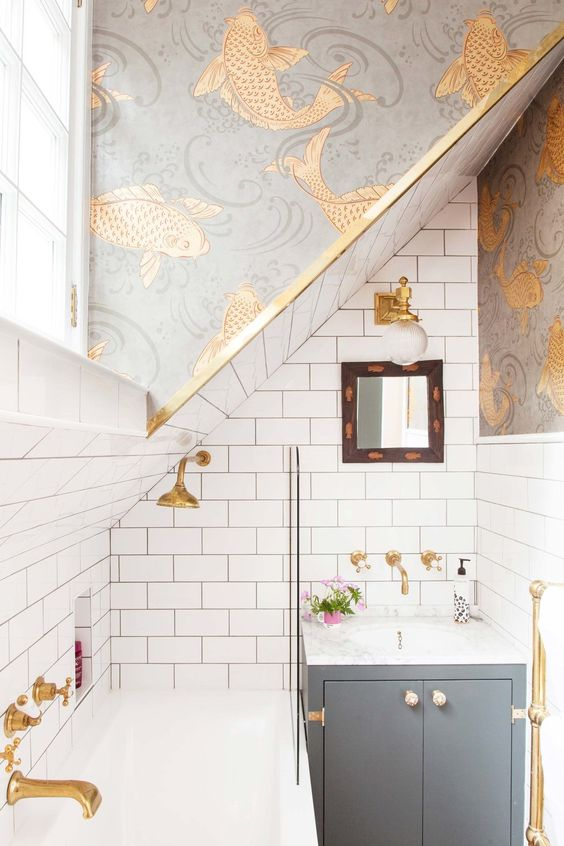 Attic family bathroom in a small space, with Osborne & Little Derwant koi carp gold fish wallpaper, Downpipe by Farrow & Ball cabinet, brass taps, metro tiles, gold and grey