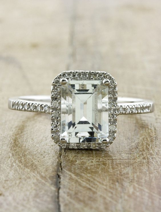 The vintage inspired Stella features a stunning 2 carat aquamarine surrounded by a halo of diamond accents in a classic cathedral setting. The emerald-cut aquamarine is a very faint blue that borders on colorless, depending on the lighting.  The shank is partially covered in diamond accents.  Created in 14k white gold.